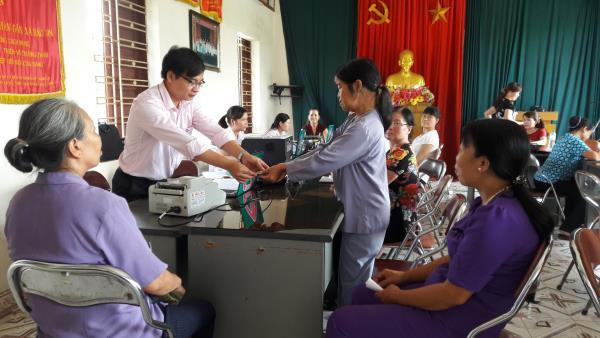 Chị Vũ Thị Rẫm, nhận tiền giải ngân nguồn vốn theo Quyết định 33/2015/QĐ-TTg từ cán bộ NHCSXH huyện An Dương